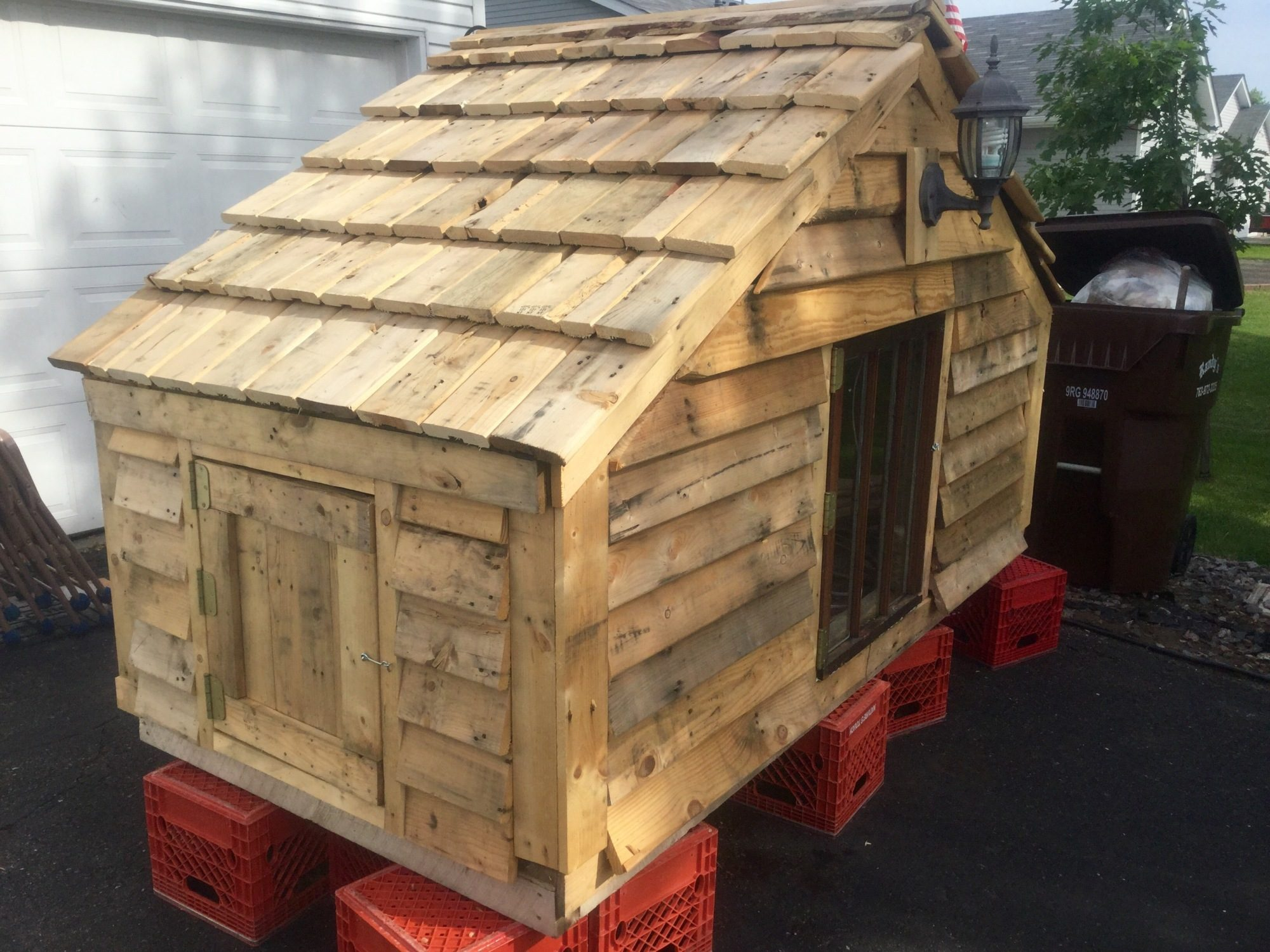 Chicken coop made from pallets. There's a light on the front and swing doors to check eggs on the ends. I found 2 antique doors for natural light front and back. There is electricity on the inside; outlet and light.